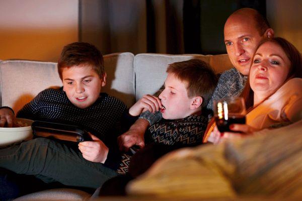 Family watching TV on sofa